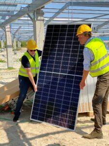 Wethouder Freek Buijtelaar en gedeputeerde Tjisse Stelpstra leggen eerste paneel grootste Nederlandse zonnepark